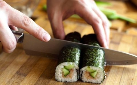 A chef cutting sushi rolls with a large knife.